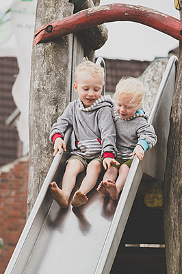 Two barefoot siblings together on a slide - p300m2114407 von Irina Heß