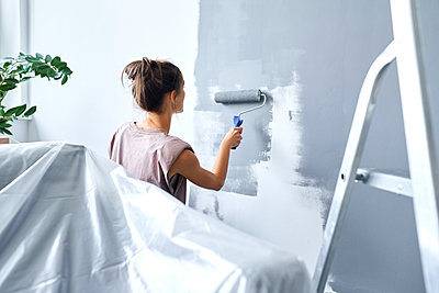 Young woman using paint roller while painting wall at home - p300m2225069 by Bartek Szewczyk