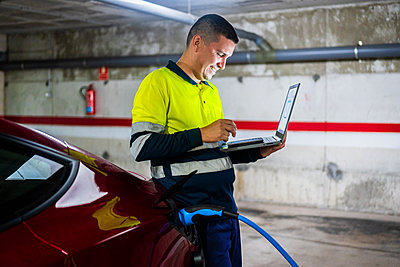 Smiling male programmer using mobile phone while leaning on electric car in auto repair shop - p300m2242463 by Javier De La Torre Sebastian