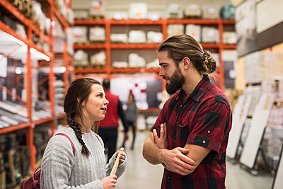 Couple discussing while standing in hardware store - p426m1407347 by Maskot