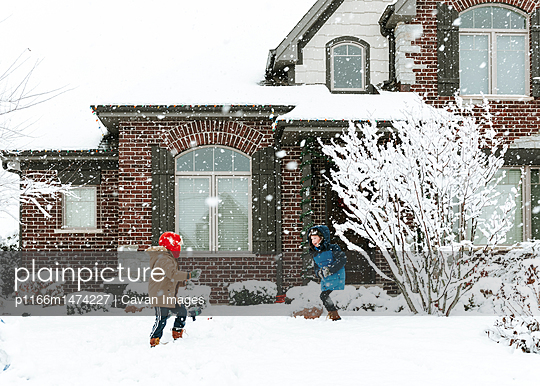 Happy brothers playing with snow in yard - p1166m1474227 by Cavan Images