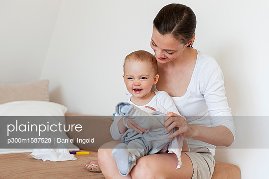 Mother putting on baby's pants at home - p300m1587528 von Daniel Ingold