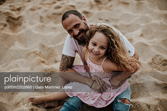 Daughter sitting on father's lap while playing at beach - p300m2202660 by Gala Martínez López