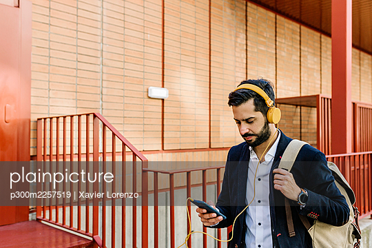 Mid adult businessman with backpack and headphones using mobile phone while standing by railing - p300m2257519 by Xavier Lorenzo
