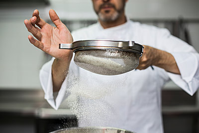 Chef sifting flour into bowl - p1166m2130212 by Cavan Images