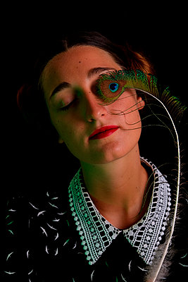 Young woman with peacock feather on face - p1521m2108351 by Charlotte Zobel