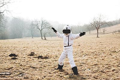 Boy wearing white space suit is posing outdoor on a meadow with virtual reality glasses - p300m2083494 von Epiximages