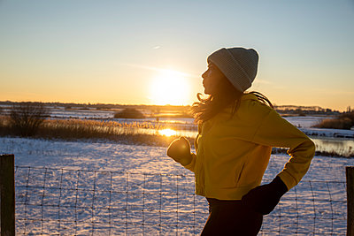 Mature woman wearing knit hat running during winter - p300m2287568 by Frank van Delft