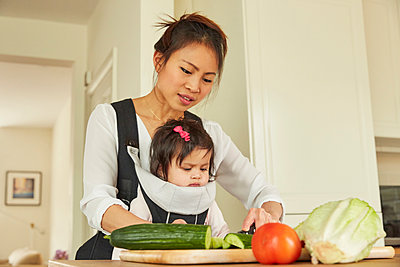 Woman with baby daughter in sling slicing salad at kitchen counter - p429m1448253 by Emma Kim