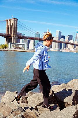 Junge Frau springt vor New York Skyline - p432m1181456 von mia takahara