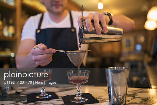 Male mixologist pouring cocktails through strainer into couple glasses in bar - p1192m1231179 by Hero Images