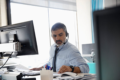 Businessman with headset working at computer in office  - p1192m2062434 by Hero Images