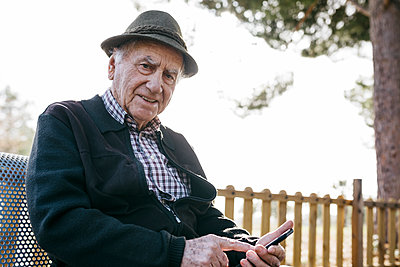 Old man with, sitting on bench, using smartphone - p300m2166561 by Josep Rovirosa