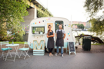 Full length portrait of confident owners standing outside food truck on street - p426m1407069 by Maskot