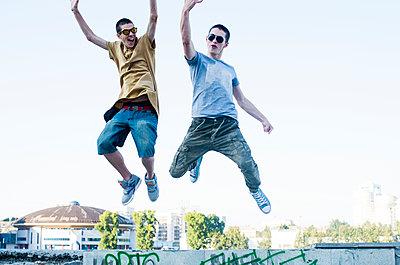 Caucasian men jumping for joy in city - p555m1420562 by Aleksander Rubtsov