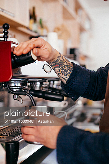 Cropped image of barista using coffee maker at cafeteria - p1185m1080948f by Astrakan