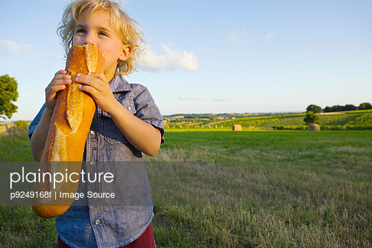 A boy eating a baguette - p9249168f by Image Source