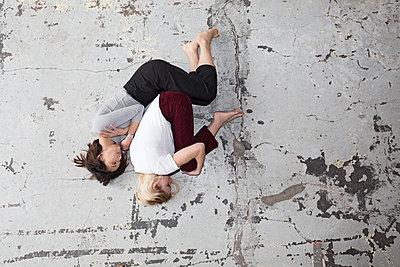 Zwei Frauen liegen in Empryostellung auf dem Boden  - p1301m2020995 von Delia Baum