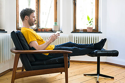 Casual man  in yellow shirt sitting in Lounge Chair in stylish apartment looking on tablet - p300m2083980 by Steve Brookland