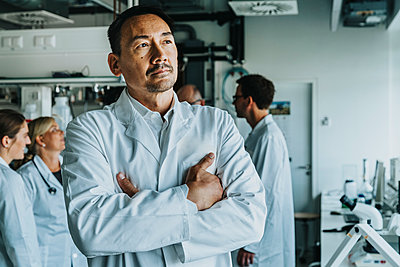 Scientist standing with arms crossed with coworkers standing and discussing in background at laboratory - p300m2226904 by Mareen Fischinger