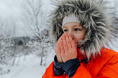 Small girl blowing on hands while looking away during winter - p300m2257014 by Oxana Guryanova