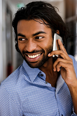Smiling young male entrepreneur talking on mobile phone in office looking away - p300m2287249 by Buero Monaco