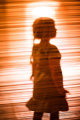 Silhouette of girl against orange background - p312m1228882 by Peter Rutherhagen