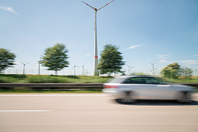 Wind farm along the highway blurred view - p335m1152371 by Andreas Körner