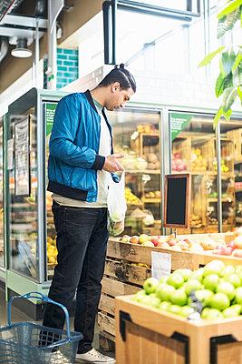 Man buying fruits in organic supermarket - p426m1407412 by Kentaroo Tryman