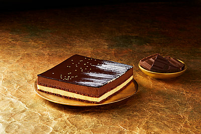 Still life with triple chocolate dessert on gold plate, christmas dessert - p429m2068740 by Danielle Wood