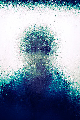 Woman looking at camera through rain splattered window - p597m2142979 by Tim Robinson