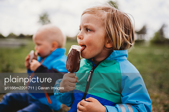 Young male kids looking to side licking chocolate popsicle ice cream - p1166m2201711 by Cavan Images