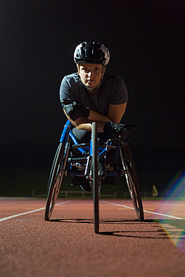 Portrait determined, tough young female paraplegic athlete training for wheelchair race on sports track at night - p1023m2067617 by Martin Barraud