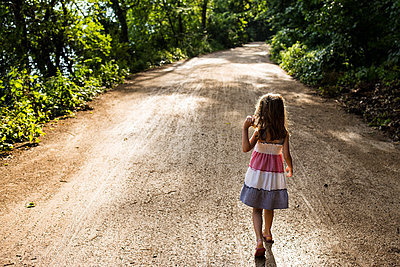 Rear view of girl walking on dirt road amidst trees in forest - p1166m1545607 by Cavan Social