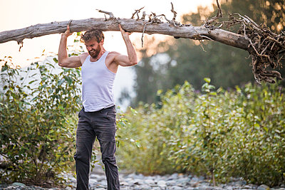 Muscular man completes a standing overhead press using a tree. - p1166m2147236 by Cavan Images
