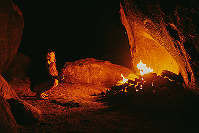 Young woman in front of camp fire at night in northern california. - p1166m2202072 by Cavan Images