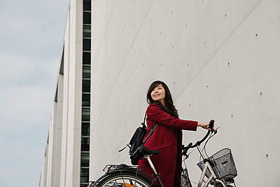 Businesswoman taking bicycle in the background of modern building - p300m2155199 by Hernandez and Sorokina