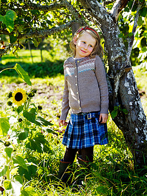 Girl leaning against apple tree - p528m742258f by Anna Kern