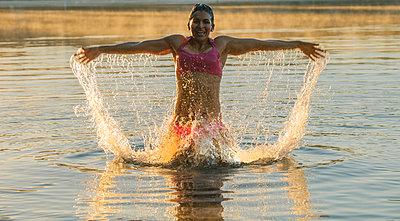 Mixed Race woman splashing in lake - p555m1302093 by Pete Saloutos