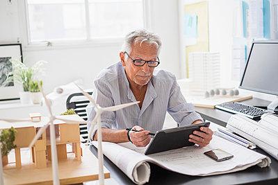 Older Caucasian architect using digital tablet in office - p555m1412285 by JGI/Tom Grill