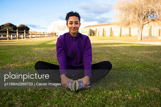 Portrait of fit and sporty young woman smiling doing stretching - p1166m2269733 by Cavan Images