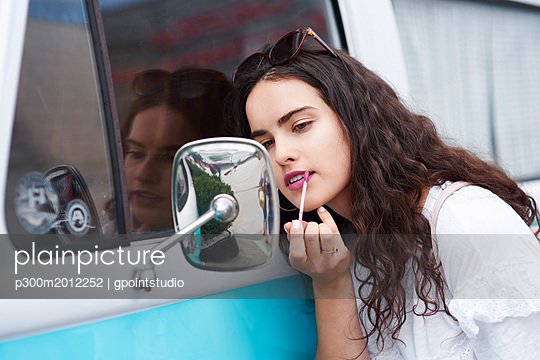 Young woman applying lipstick looking in wing mirror of a van - p300m2012252 von gpointstudio