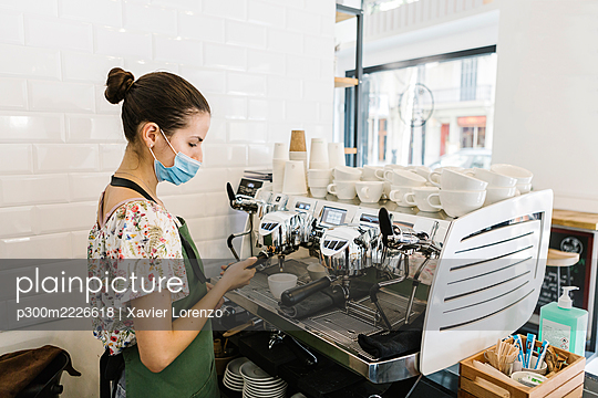Young woman with face mask making coffee while standing in kitchen at coffee shop - p300m2226618 by Xavier Lorenzo