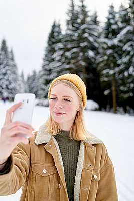 Young woman takes a selfie in the snow - p1124m1589307 by Willing-Holtz