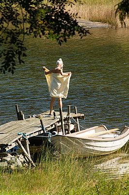 Woman drying off after swim  - p1418m2014891 by Jan Håkan Dahlström