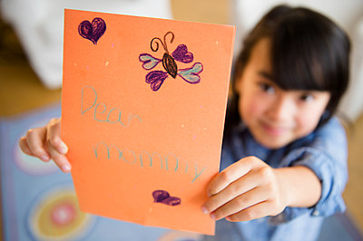 Close up of Filipino girl holding card for mother - p555m1415584 by JGI/Jamie Grill
