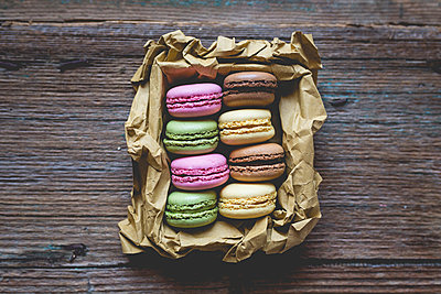 Different macarons in a box on wood - p300m1228259 by Giorgio Fochesato