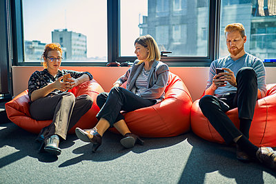 Colleagues with cell phones sitting in bean bags in office lounge - p300m2062935 by Zeljko Dangubic
