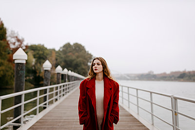 Portrait of young woman wearing red coat on a bridge during rainy day - p300m2160335 von Tania Cervián