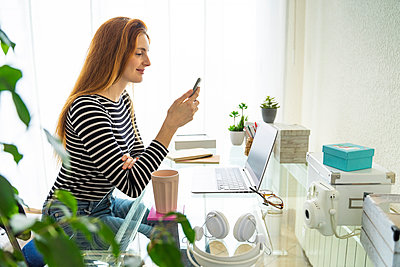 Young woman using smartphone at desk at home - p300m2179944 by VITTA GALLERY